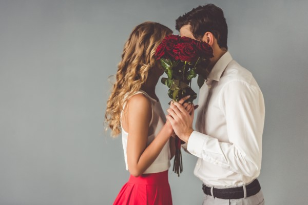 man giving roses to woman